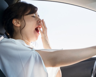 Young woman yawning in car
